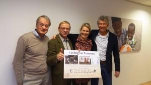 Three Dutch cycling team members (Maarten Van den Belt, Albert de Vries and Rob Manassen) handing over a cheque for the money raised to Marike van Seetert (Director: Homeplan).
