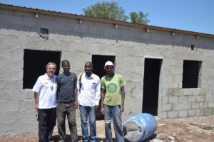 Bishop Jose Ponce de Leon, with Machawe Ngcamphalala of the Diocese of Manzini (second from right) and two trainees, during construction of Mrs Makhubela's new house.