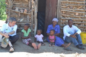 Bishop Jose Luis Ponce de Leon with Mrs Makhubela – a widow who looks after her six orphaned grandchildren – in front of their old hut.